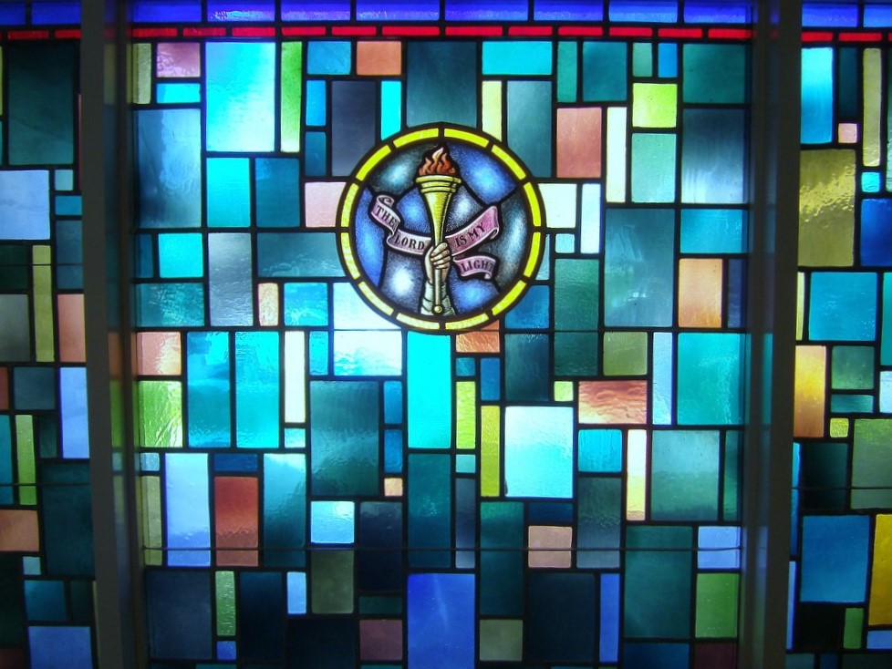 """Stained-glass window from Boerne United Methodist Church showing hand with torch and legend """"The Lord is my light"""""""