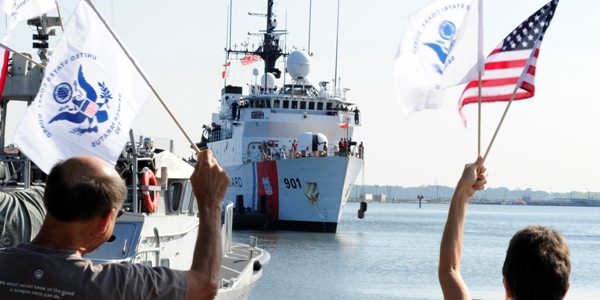 Flag-waving family members welcome home the crew of the Coast Guard Cutter Bear