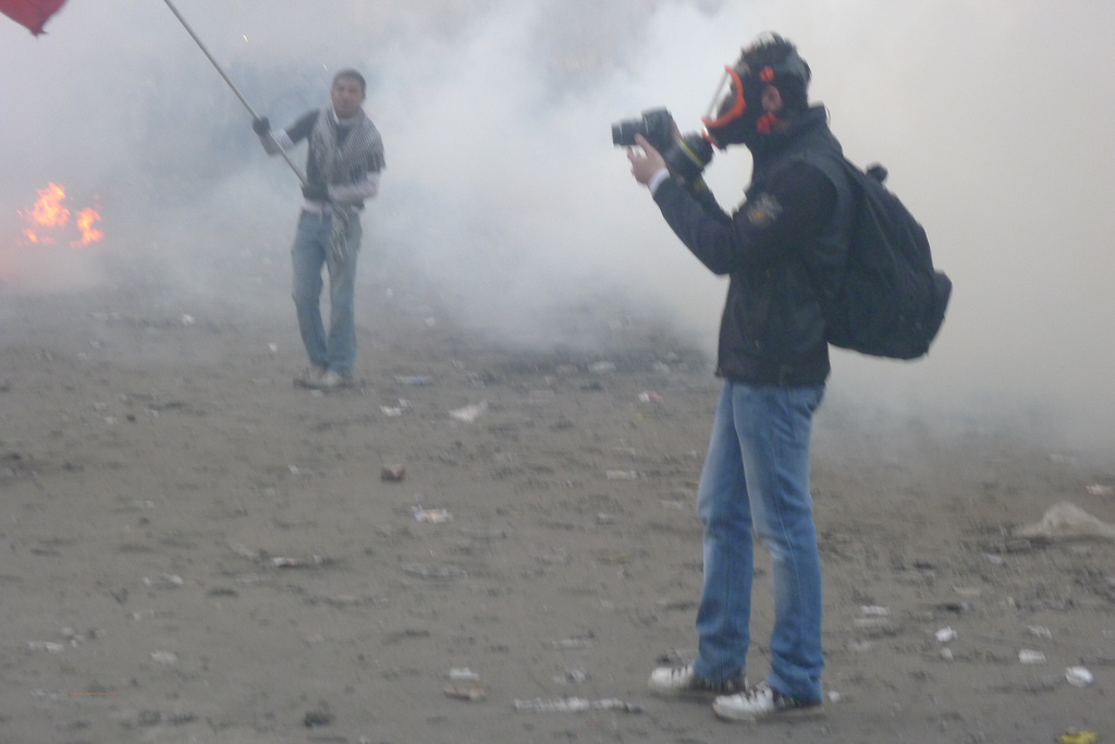 Person wearing gas mask and taking photos, surrounded by clouds of gas, with flames and flag-waving demonstrators in the background
