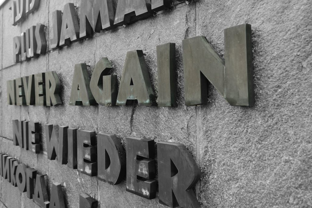 """A wall at the Dachau Concentration Camp in Munich, Germany, reads """"Never again"""" in five different languages."""