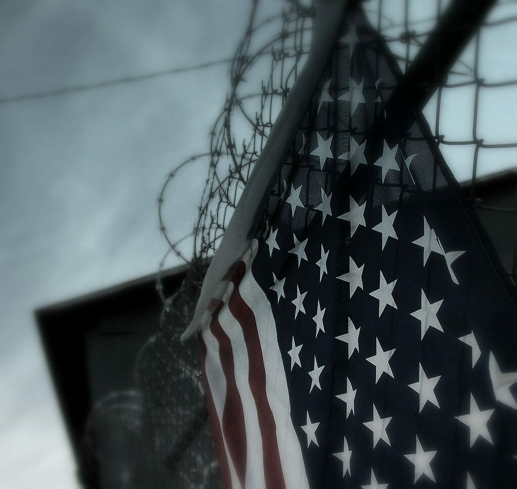 American flag draped from a razor wire fence
