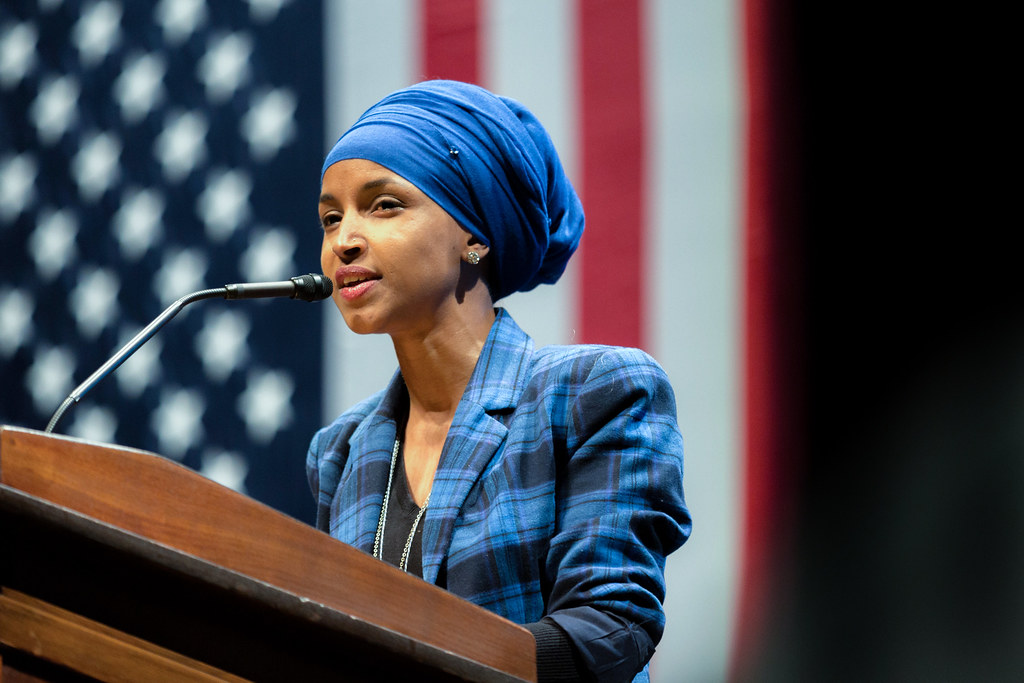 Ilhan Omar speaking at podium in front of American flag