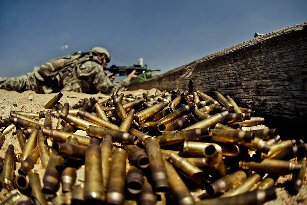 Spent shell casings pile up in the foreground as a soldier in the background fires a machine gun