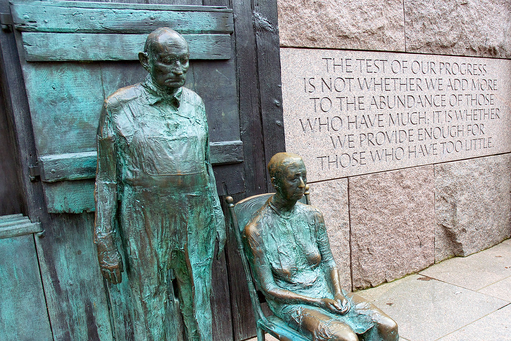 "Statues of depression-era farming couple with FDR quote: ""The test of our progress is not whether we add more to the abundance of those who have much; it is whether we provide enough for those who have too little."""