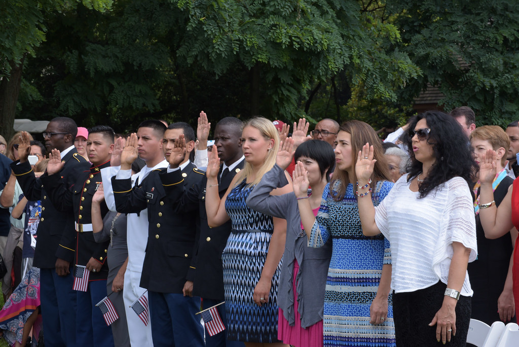 A diverse group of men and women take the oath of citizenship at a naturalization ceremony.