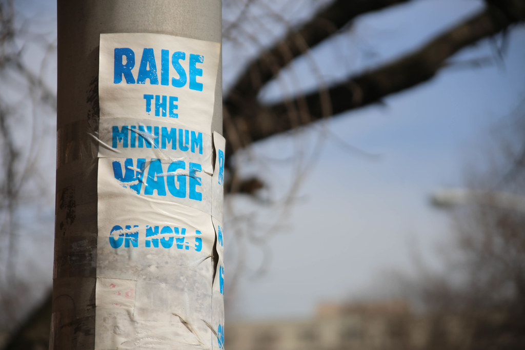 "A weather-beaten sign reading ""Raise the minimum wage"" taped to a lamppost"