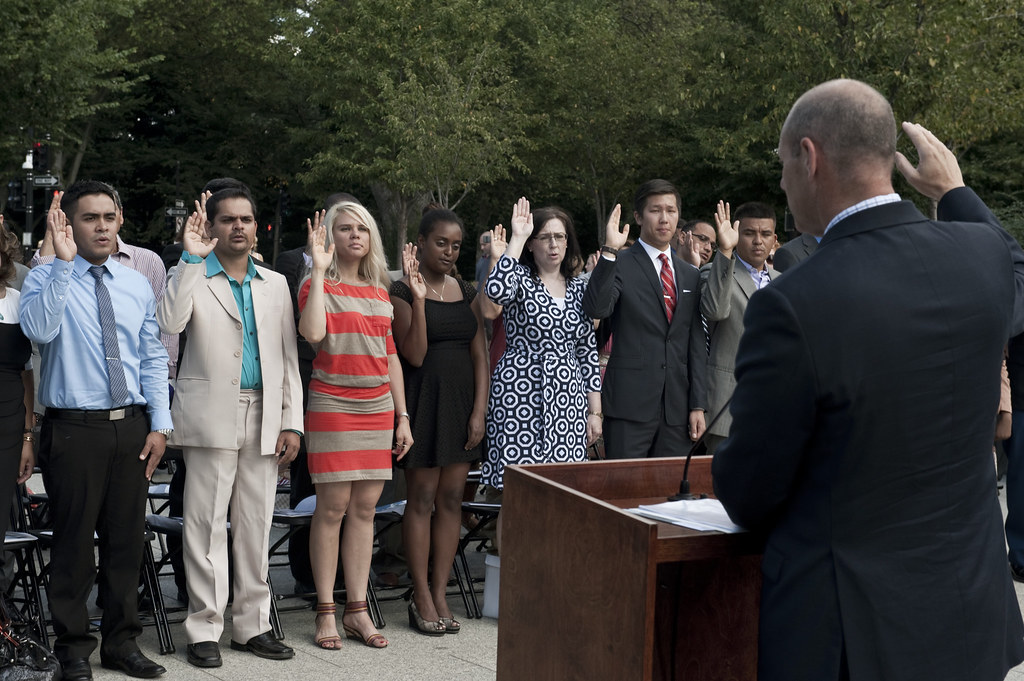 A diverse crowd of people takes the oath of United States citizenship