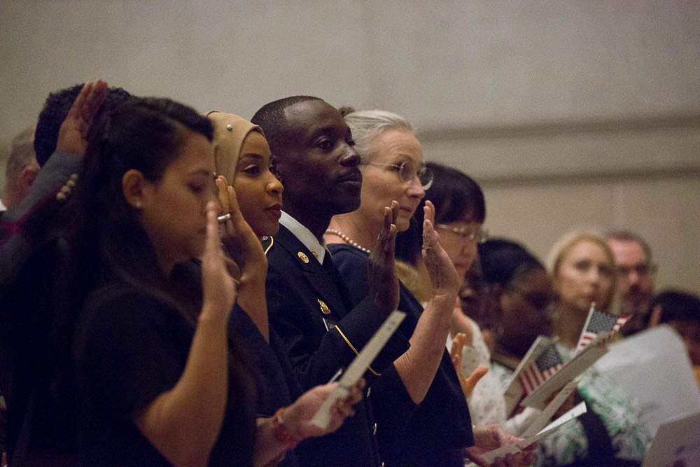 A diverse row of citizenship candidates hold up their right hands as they take the citizenship oath