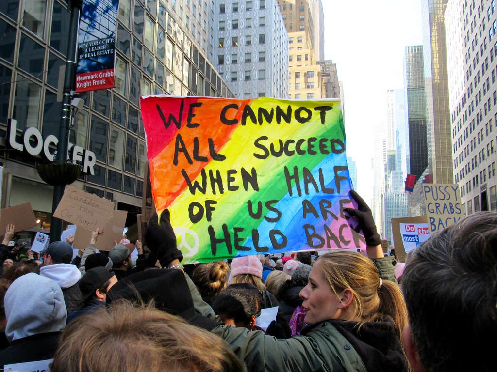 "In the midst of a crowd, a woman holds up a rainbow-colored sign reading ""We cannot all succeed when half of us are held back."""
