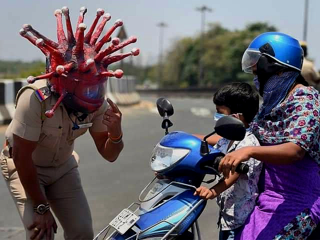 A policeman in a helmet designed to look like a coronavirus cell points to his helmet while speaking to a mother and son an a scooter, encouraging them to return home.