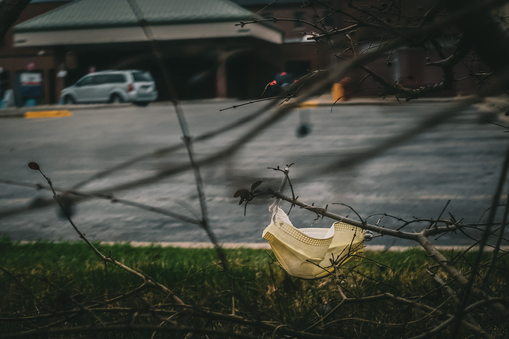 A discarded facemask is tangled in a bush, with parking lots and buildings in the background