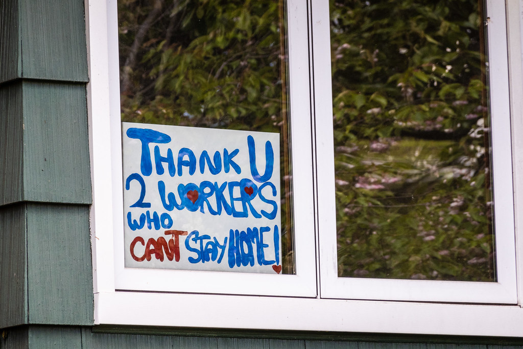 """Handpainted sign in window of house reads, """"Thank U 2 workers who can't stay home!"""""""