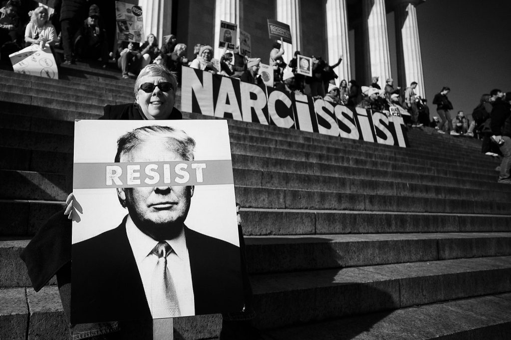 """Protest on Capital hill. Signs spell out the word """"Narcissit"""" and """"Resist"""""""