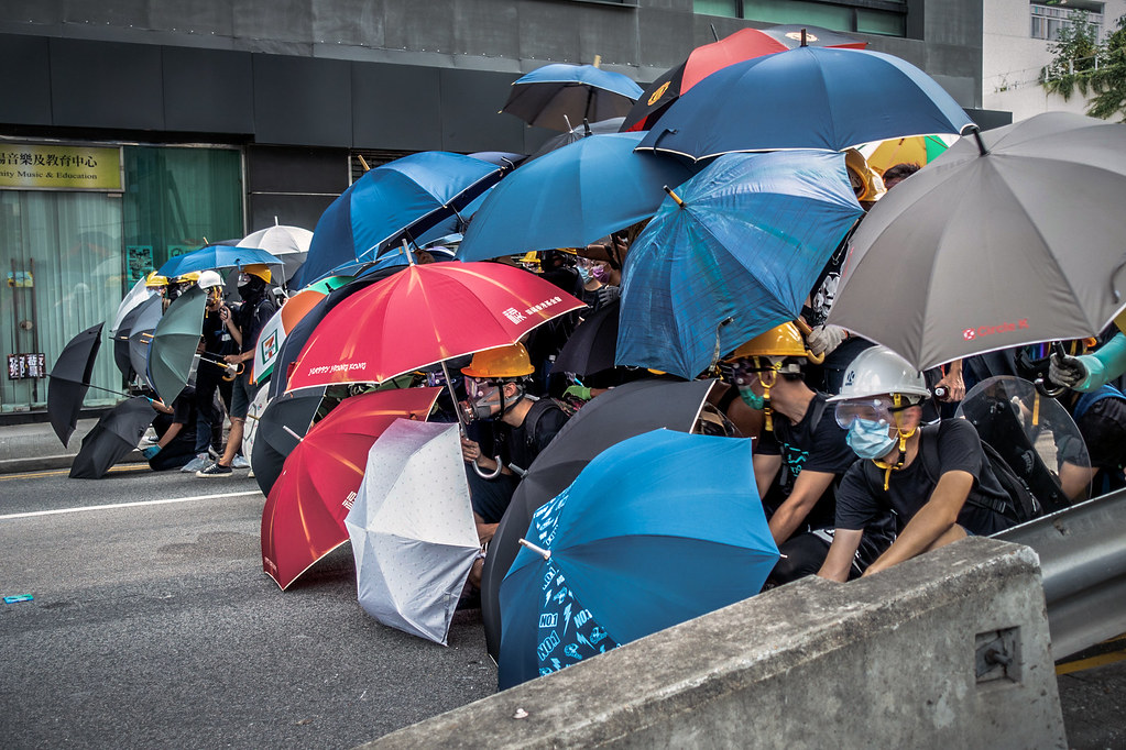 Protestors with masks and hardhats form a line, protecting themselves with umbrellas