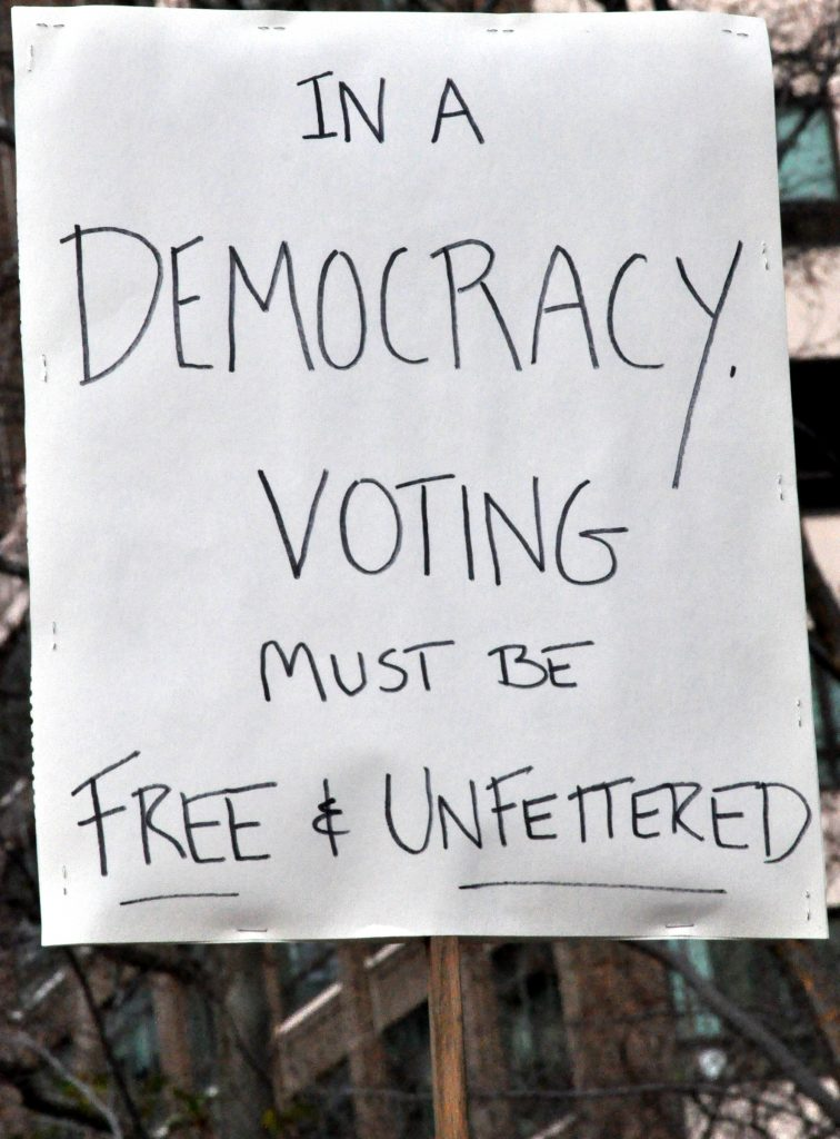 Sign of a protester which reads 'In a Democracy, voting must be free and unfettered""