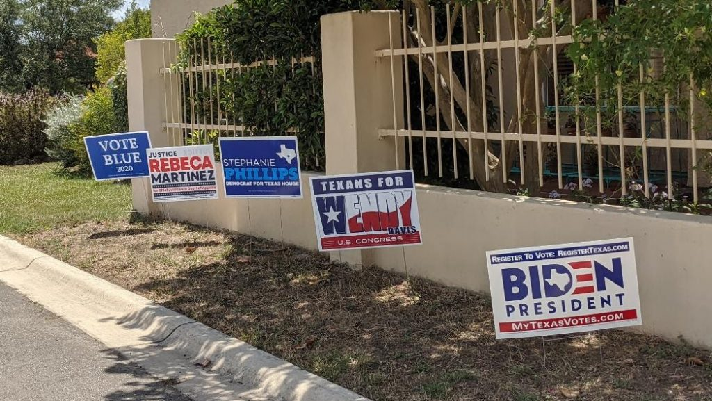 A row of campaign signs in a yard: Biden for President, Texans for Wendy Davis, Stephanie Phillips for HD73, Rebeca Martinez for Judge, Vote Blue 2020