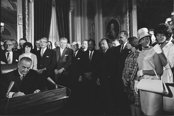 President Lyndon Johnson signs the Voting Rights Act as Martin Luther King, Jr., and other civil rights leaders look on
