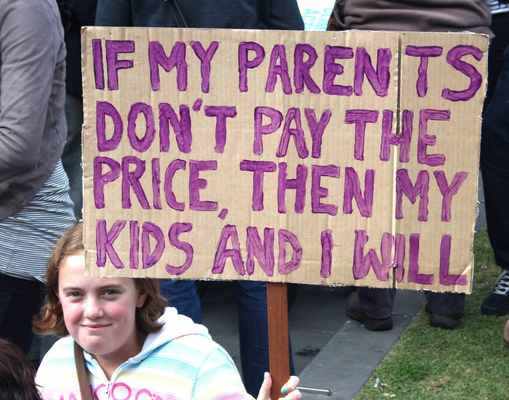 """Young girl holding a poster that says """"If my parents don't pay the price, then my kids and I will"""""""