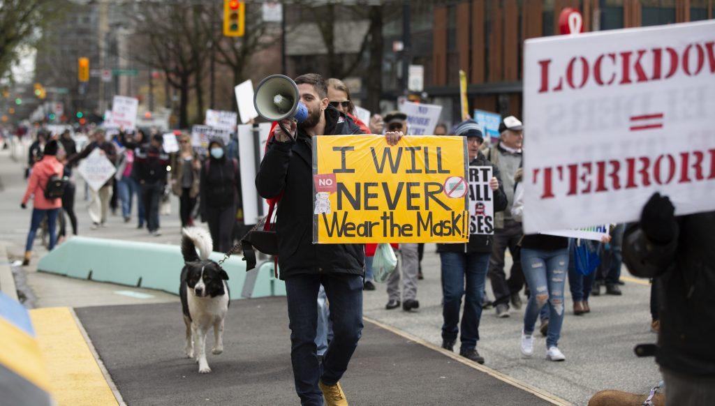 """Anti-mask protest. Man with a sign which reads """"I will never wear the mask!!"""""""
