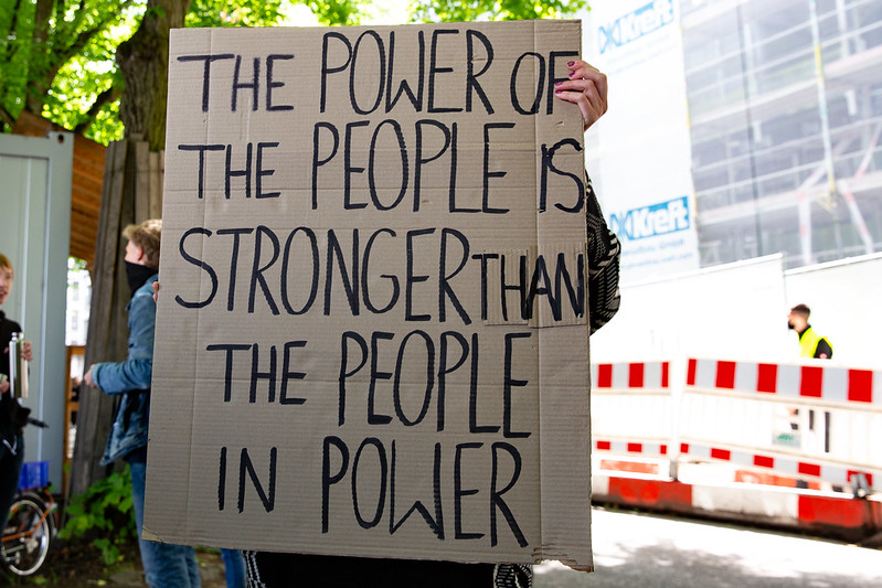 """Sign which reads """"The power of the people is stronger than the people in power"""""""