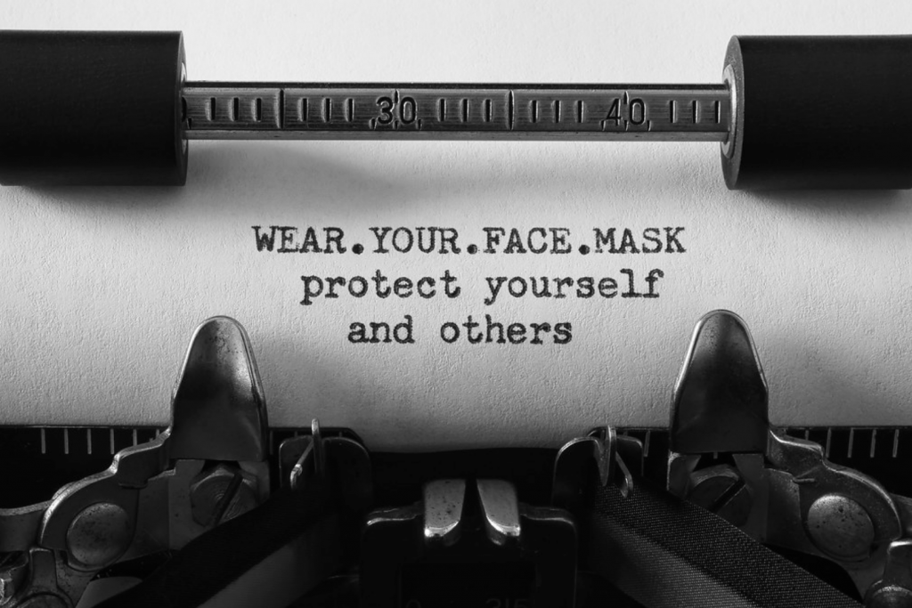 """Closeup of a typewritter and paper with the message """"WEAR.YOUR.FACE.MASK protect yourself and others"""" typed on the paper."""